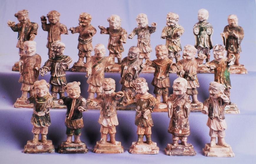 Kích thước : H: 10,4 cm. Chất liệu : Sứ Niên đại : Thế kỷ XVII (Thời Khang Hy)Xuất xứ : Trung Hoa (thời Khang Hy)Tình trạng : Sứt nhỏSố kiểm kê : Mô tả:Sưu tập tượng sứ men màu : gồm 21 tượng nam mặc áo choàng đứng trên bệ với nhiều tư thế. Lớp men phủ màu nâu, xám xanh đậm nhạt khác nhau.